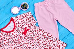 Toddler girl summer clothes close up. Baby girl cotton apparel and hairbrush on blue wooden background. Child summer fashion royalty free stock photo