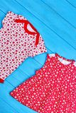Toddler girl summer cotton clothes. Infant baby girl brand summer clothing in red tone, blue wooden background. Patterned organic clothes for newborn girl royalty free stock image