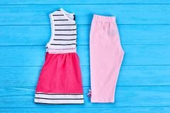 Toddler girl summer cotton clothes. New collection of summer clothing for little girls on blue wooden background. Kids fashion style royalty free stock photo