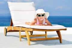 Toddler girl on sunbed. Adorable toddler girl relaxing on sunbed Royalty Free Stock Photo