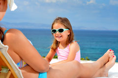 Toddler girl on sunbed. Adorable toddler girl relaxing on sunbed with her mother Royalty Free Stock Image