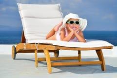 Toddler girl on sunbed. Toddler girl relaxing on sunbed Royalty Free Stock Photo