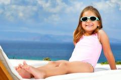 Toddler girl on sunbed. Toddler girl relaxing on sunbed Royalty Free Stock Photography