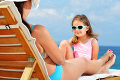Toddler girl on sunbed. Toddler girl relaxing on sunbed with her mother Royalty Free Stock Photo