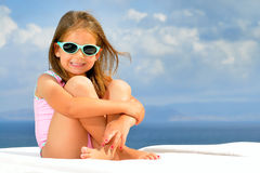 Toddler girl on sunbed Stock Images