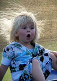 Toddler girl is surprised. Toddler girl with blond hair, mouth open in surprise. Her hair is spread out in the sun stock image