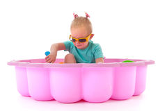 Toddler girl in swimming pool. Toddler girl playing in swimming pool isolated over white background royalty free stock image