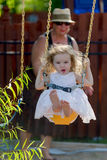 Toddler Girl on the Swing pushed by her Grandmother. Toddler girl having fun on the swing while having candy with her bare naked feet and pushed by her Royalty Free Stock Image