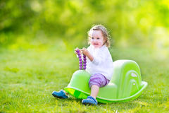 Toddler girl on a swing in a sunny garden Royalty Free Stock Photos