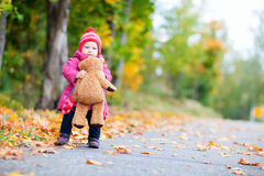 Toddler girl with teddy bear outdoors Royalty Free Stock Image