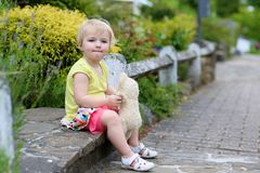 Toddler girl with teddy bear on the street Stock Photo