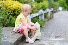 Toddler girl with teddy bear on the street Stock Photos