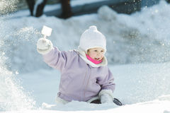 Toddler girl tossing up natural snow with plastic Stock Images