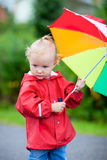 Toddler girl with umbrella outdoors on rainy day Stock Photo