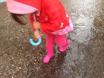 Toddler girl with umbrella outdoors at rainy day Royalty Free Stock Photos