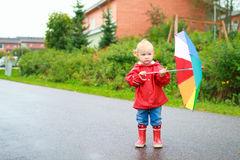 Toddler girl with umbrella outside on rainy day Stock Images