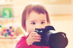 Toddler girl using playing with a camera Royalty Free Stock Photos