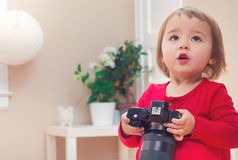 Toddler girl using playing with a camera Royalty Free Stock Photo