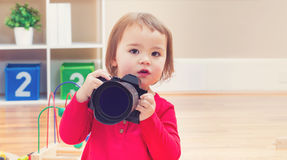 Toddler girl using playing with a camera Stock Photos