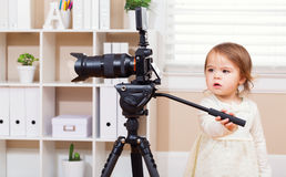Toddler girl using a professional camera Royalty Free Stock Photo