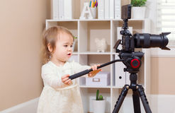 Toddler girl using a professional camera Royalty Free Stock Image