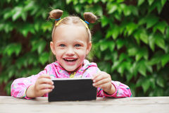 Toddler girl using a smart phone Royalty Free Stock Photography