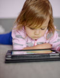Toddler girl using tablet pc Stock Image