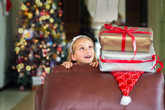 Toddler girl waiting for surprise from gift present on Christmas Stock Photos