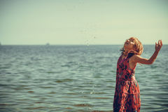 Toddler girl wearing dress playing in water Royalty Free Stock Images