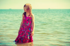 Toddler girl wearing dress playing in water Royalty Free Stock Photo