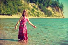 Toddler girl wearing dress playing in water Royalty Free Stock Image