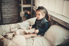 Toddler Girl Wearing Long-sleeved Top Reading Book While Sitting on Bed stock images