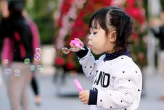 Toddler Girl Wearing White and Black Sweater Holding Plastic Bottle of Bubbles at Daytime Stock Image