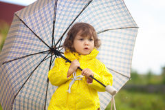 Toddler girl wearing yellow waterproof coat with checkered umrel Royalty Free Stock Image