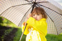 Toddler girl wearing yellow waterproof coat with chekered umbrel. stock photography