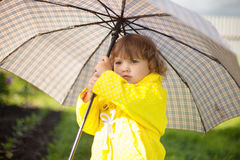 toddler girl wearing yellow waterproof coat with chekered umbrella stock images