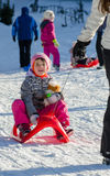 Toddler girl in winter suit on sleigh pulled by woman on slope Royalty Free Stock Images