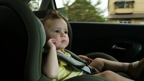 Toddler girl yawns in dark green child car safety seat stock image