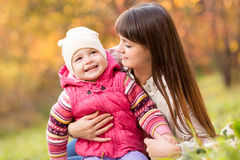 Toddler girl and young mother play in the autumn park Stock Images