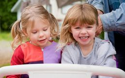 2 Toddler Girls Playing Outside in Toy Car Stock Photo