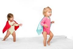 portrait of pretty toddler girls in superhero capes stock image