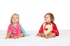 Toddler girls in superhero capes. Portrait of pretty toddler girls in superhero capes isolated on white royalty free stock photography