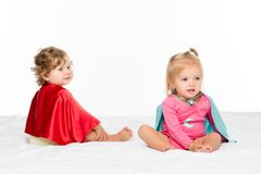 Toddler girls in superhero capes. Portrait of pretty toddler girls in superhero capes isolated on white royalty free stock image