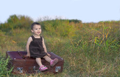 Toddler going on vacation. Cute little girl with her old and big suitcase Stock Images