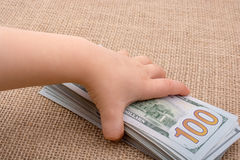 Toddler hand holding banknote bundle of US dollar in hand Royalty Free Stock Photography