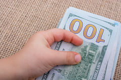 Toddler hand holding banknote bundle of US dollar in hand Stock Photos
