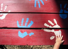 Toddler Hand on Paint Hands. A toddler hand reaching out to painted hands on a painted picnic table royalty free stock images