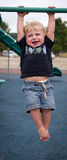 Toddler hanging from bars. Toddler hanging from monkey bars stock image