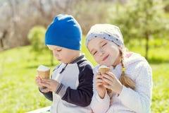 Toddler happy children eating ice cream. In spring Stock Photos