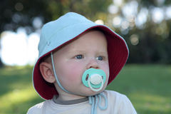 Toddler in hat with pacifier. Portrait of male toddler outdoors in sunhat with pacifier royalty free stock image